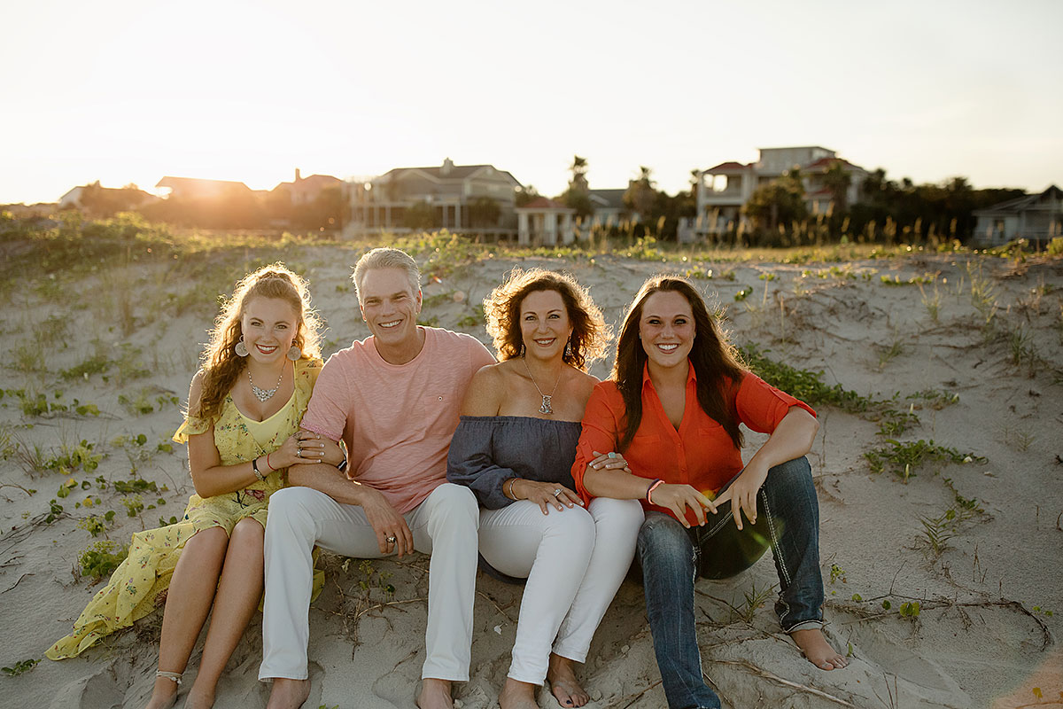 Brad D. Smith sits on the beach with his wife, Alys, and their two daughters, Payton and Devon.